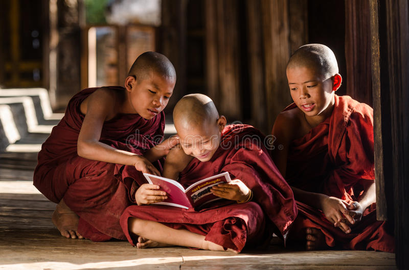 Group of Burmese young monks reading book in temple. Group of Burmese novices, young monks, reading book in the temple at Mandalay, Myanmar stock photography