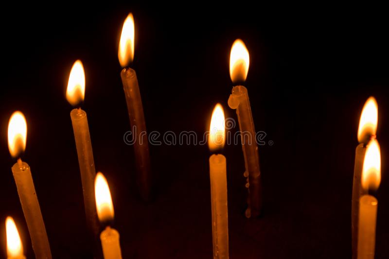 Group of burning candles in dark stock photography