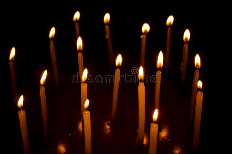 Group of burning candles in dark royalty free stock photography