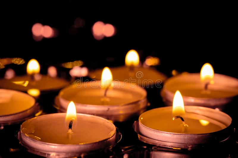 A group of burning candles with soft focus in the back royalty free stock photo