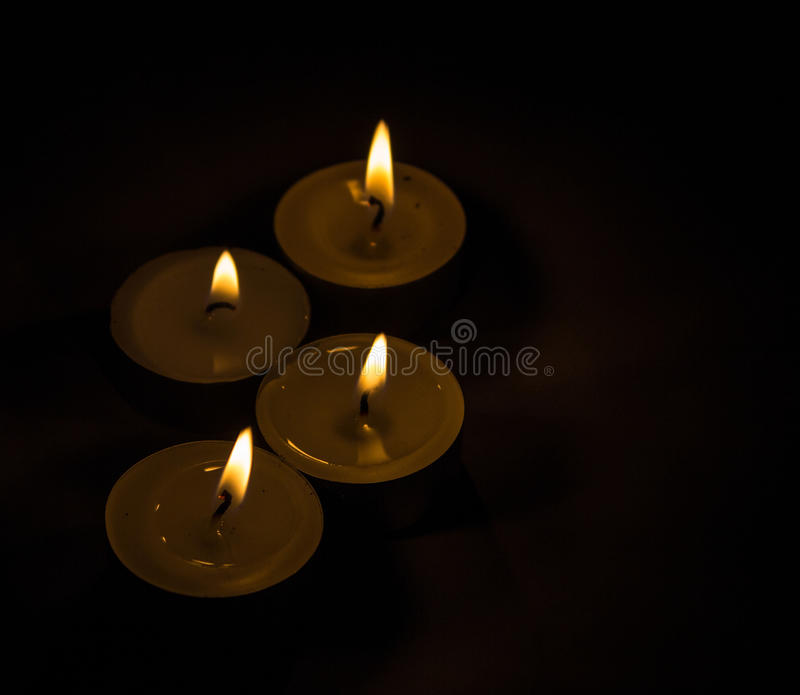 Group of burning small candles on a black background. Group of burning small round candles on a black background royalty free stock photos