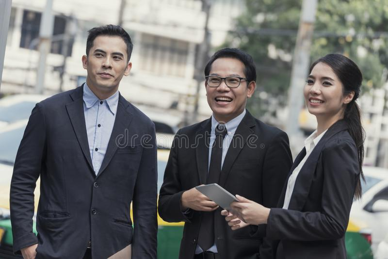 Group of business asian partner discussing while walking in office building. colleague social concept stock photography