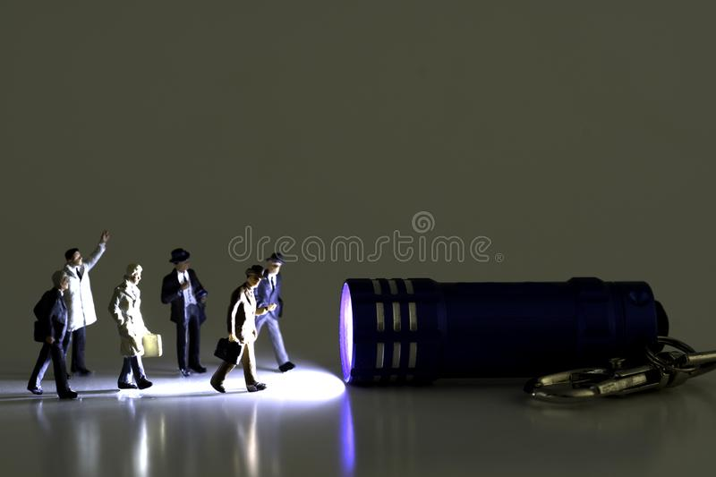 Group Of Business Figurines walking towards a stream of light from a miniature blue flashlight royalty free stock images