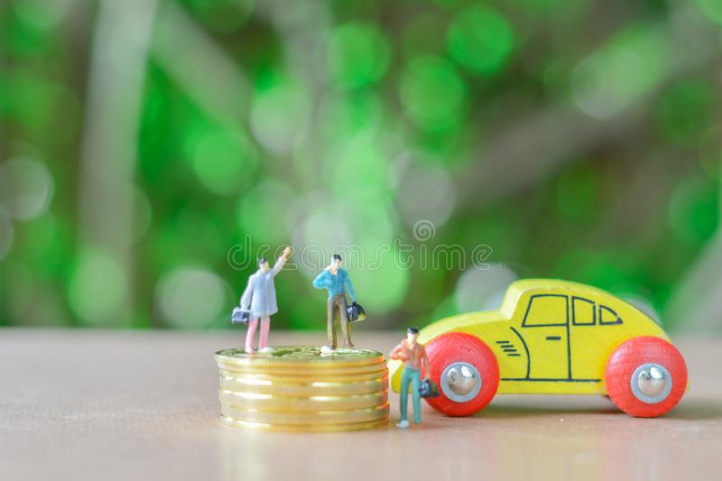 Group of business man Miniature people, small model human figure sell or buy wooden yellow car and stack of gloden coins with royalty free stock photo
