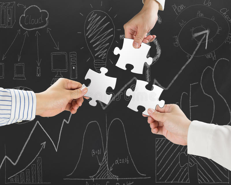 Group of business people assembling blank white jigsaw puzzles. On business concept doodles background stock photo