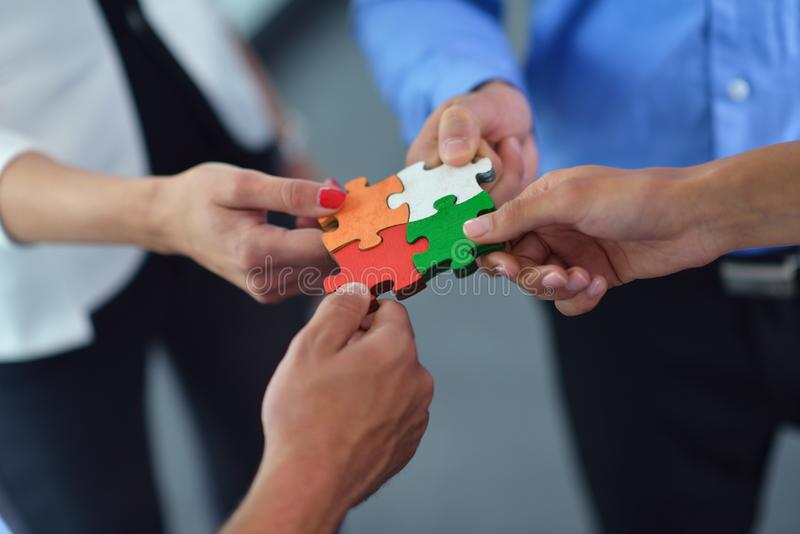 Group of business people assembling jigsaw puzzle royalty free stock photography