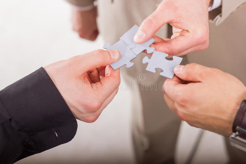 Group of business people assembling jigsaw puzzle. Teamwork. royalty free stock image