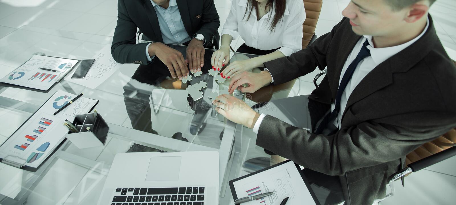 Group of business people assembling the pieces of the puzzle stock photos