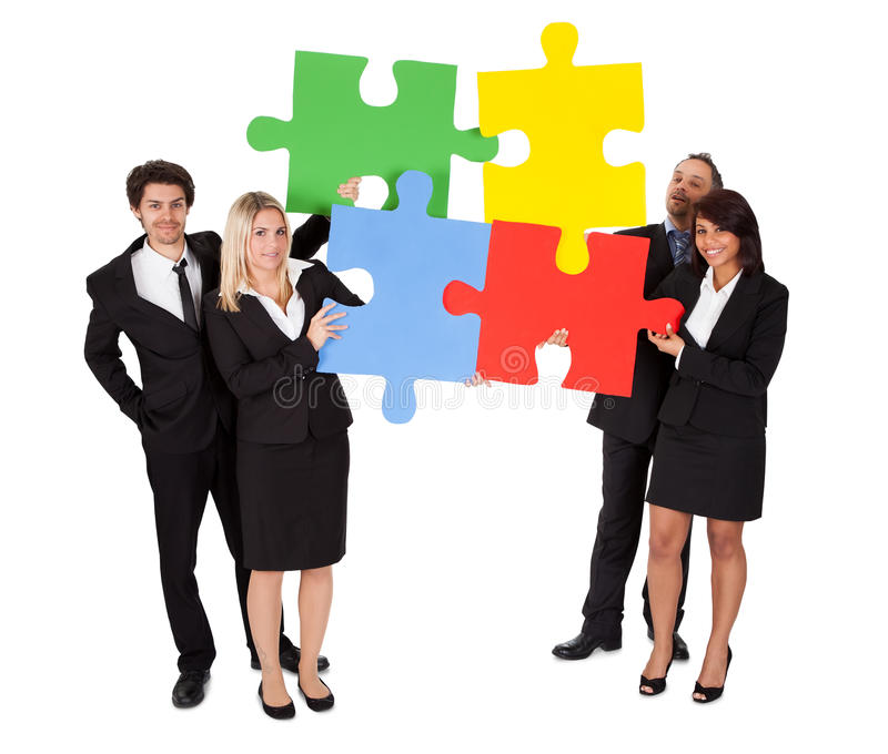 Group of business people assembling puzzle stock photo