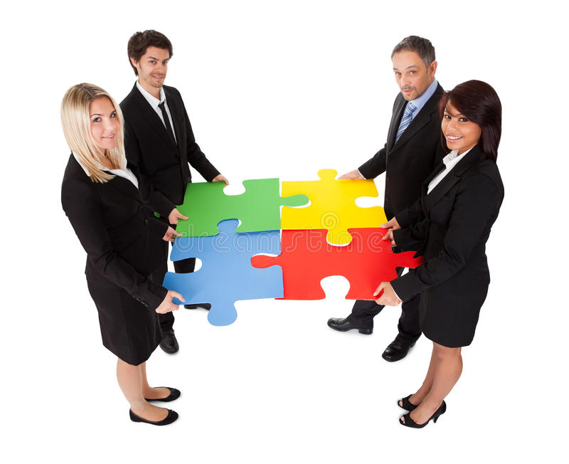 Group of business people assembling puzzle stock images
