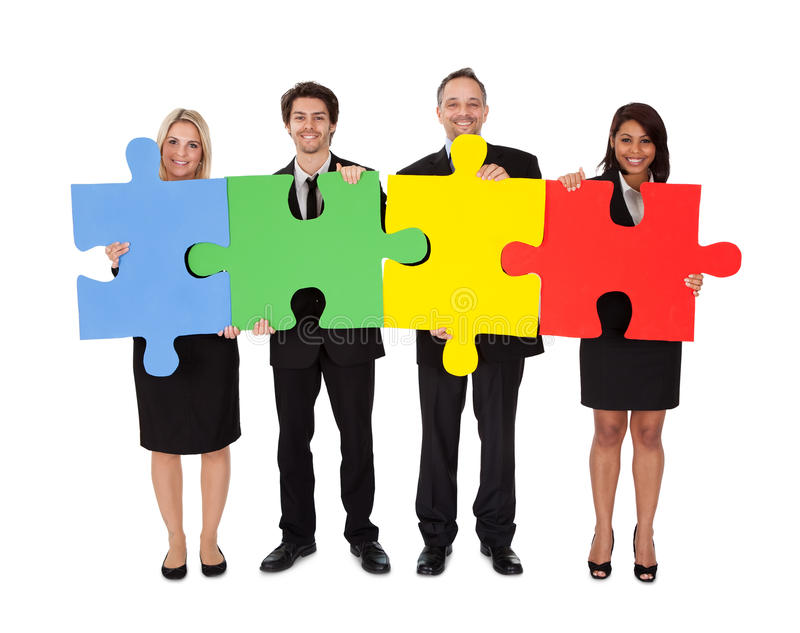 Group of business people assembling puzzle royalty free stock photo