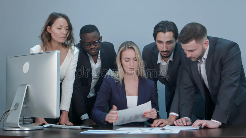 Group of business people busy discussing financial matter during meeting, standing around female boss desk stock photography
