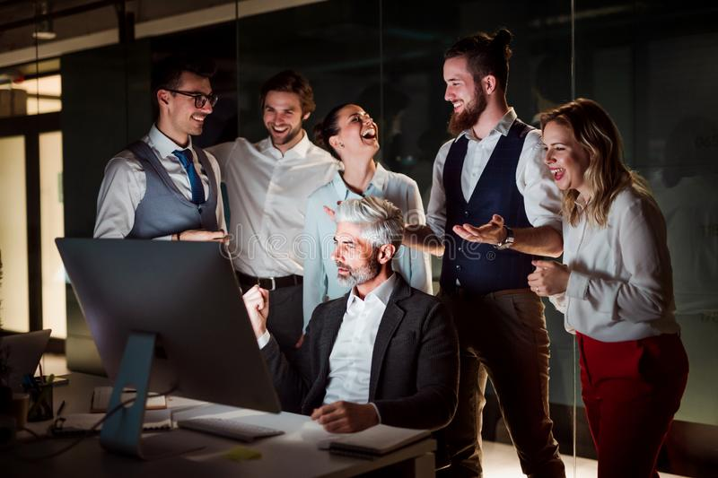 A group of business people with computer in an office, expressing excitement. stock photography
