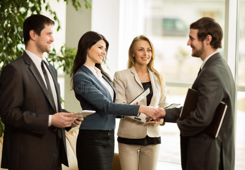 Group of business people congratulating their handshaking colleagues stock photography