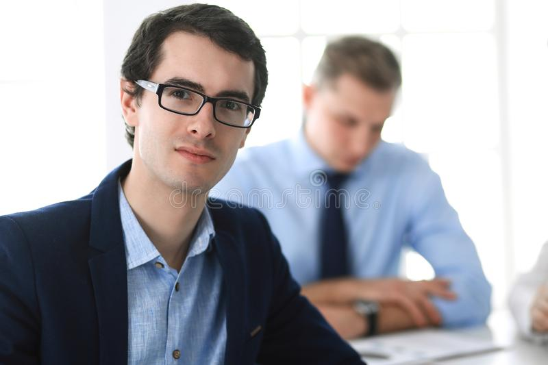 Group of business people discussing questions at meeting in modern office. Headshot of businessman at negotiation royalty free stock photo