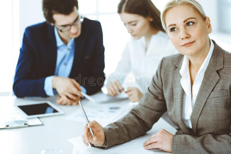 Headshot of business woman at negotiation. Group of business people discussing questions at meeting in modern office stock photo