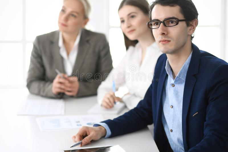 Group of business people discussing questions at meeting in modern office. Managers at negotiation or brainstorm stock images