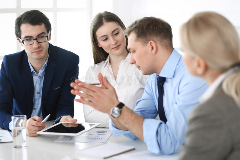 Group of business people discussing questions at meeting in modern office. Managers at negotiation or brainstorm stock photography