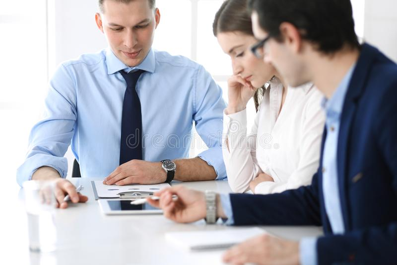 Group of business people discussing questions at meeting in modern office. Managers at negotiation or brainstorm stock photos