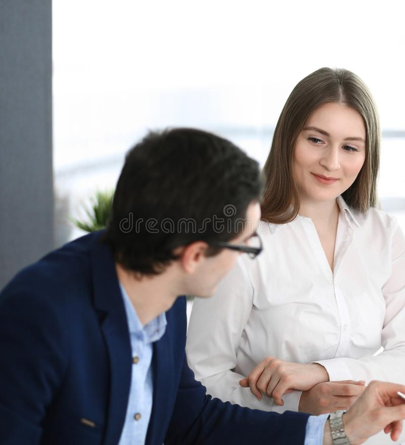 Group of business people discussing questions at meeting in modern office. Managers at negotiation or brainstorm stock image