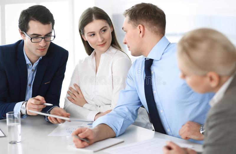 Group of business people discussing questions at meeting in modern office. Managers at negotiation or brainstorm royalty free stock image