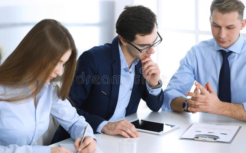 Group of business people discussing questions at meeting in modern office. Managers at negotiation or brainstorm royalty free stock photography