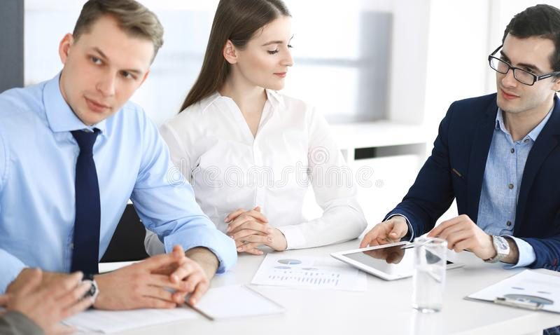 Group of business people discussing questions at meeting in modern office. Managers at negotiation or brainstorm stock photo