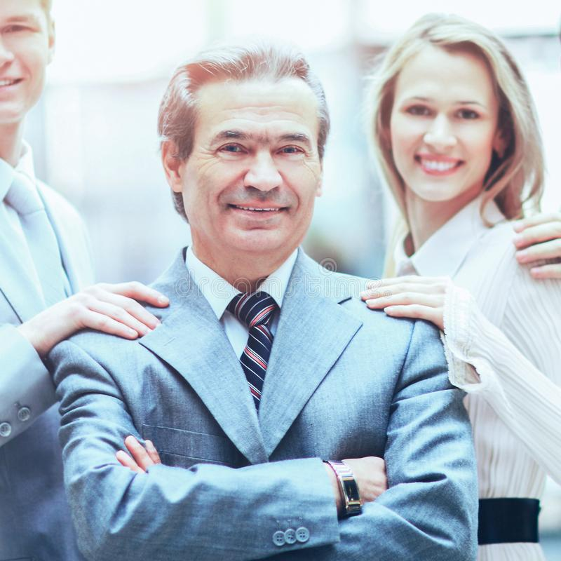 Group of business people facing each other with the leader  a businessman in the foreground. Group of business people with businessman leader on foreground stock photo