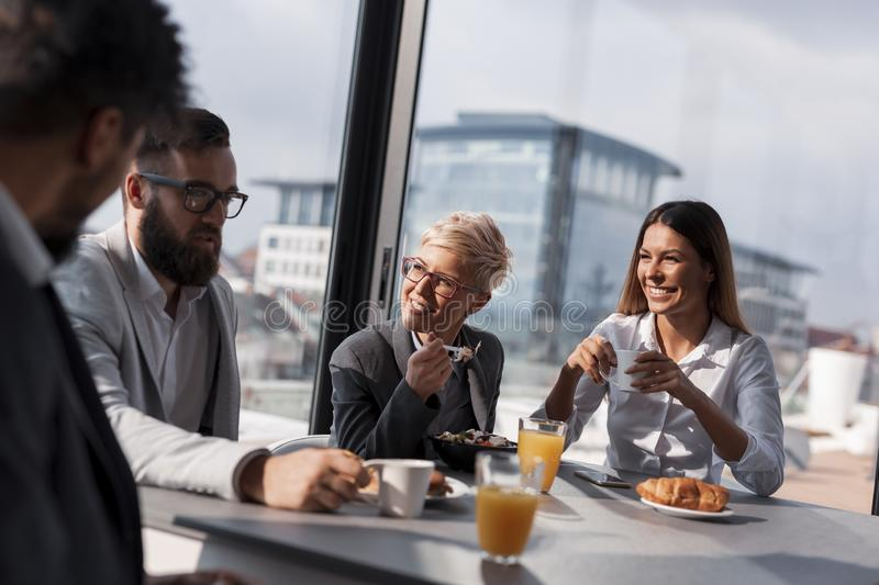 Working breakfast. Group of business people having breakfast in company`s restaurant. Focus on the women in the middle royalty free stock image