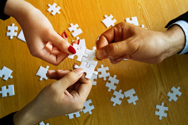 Group of business people help to assembling jigsaw puzzle stock photos