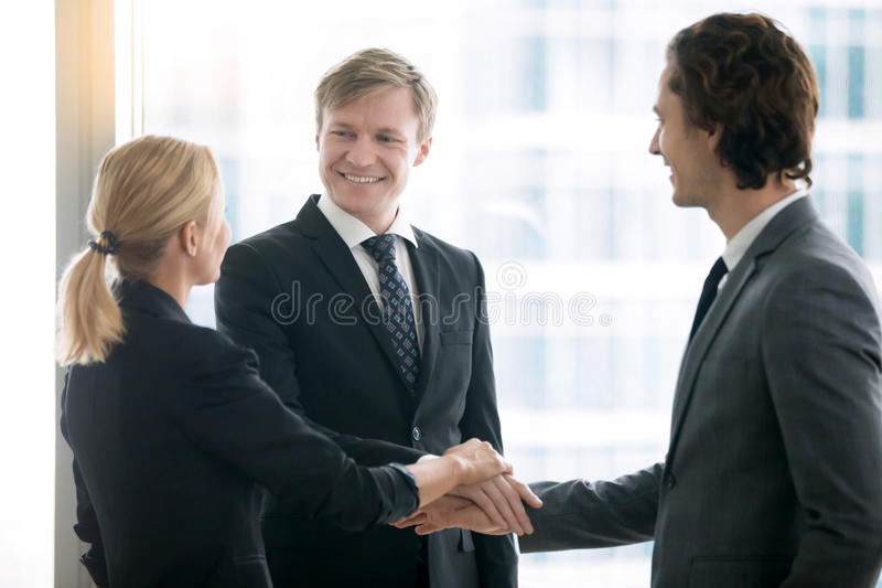 Group of business people, holding hands in a pile stock photo