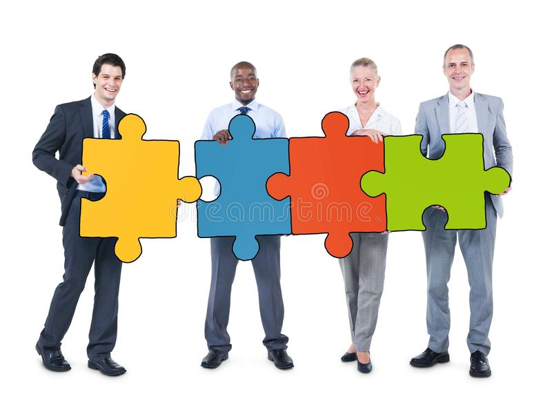 Group of Business People Holding Puzzle Pieces royalty free stock image