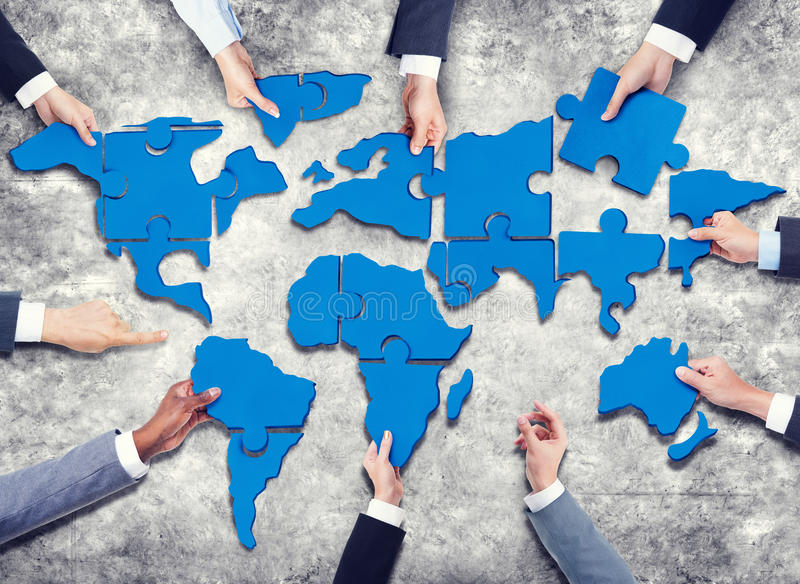 Group of Business People with Jigsaw Puzzle Forming in World Map.  royalty free stock photography