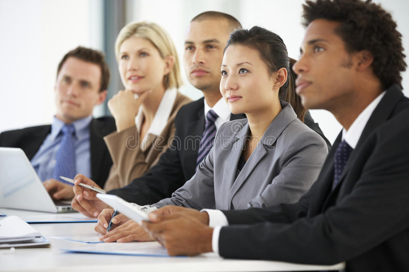 Group Of Business People Listening To Colleague Addressing Office Meeting stock photo