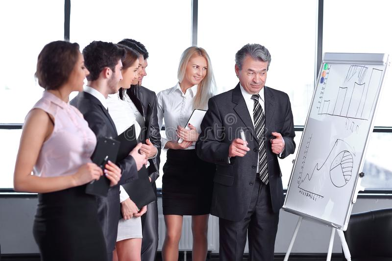 Group of business people looking at the graph on flipchart. A group of business people looking at the chart on the flipchart. start-up stock photos