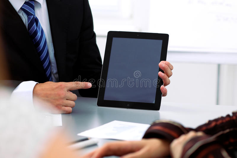 Group of business people at meeting, close up. Boss pointing into tablet computer monitor royalty free stock images