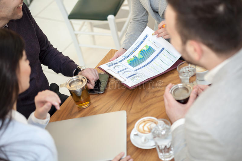 Group of business people meeting in coffee shop and holding a b stock photos