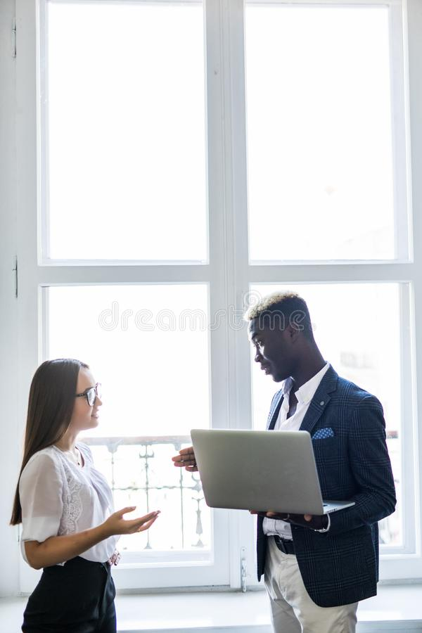 Group of business people, afro man in a suit and asian woman holding a laptop in front of office window on the background stock images