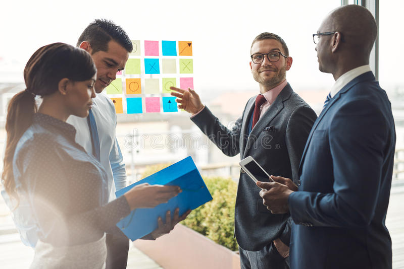 Group of business people with notes on window. Young group of diverse business people in conference meeting using colorful sticky notes to organize ideas on stock image