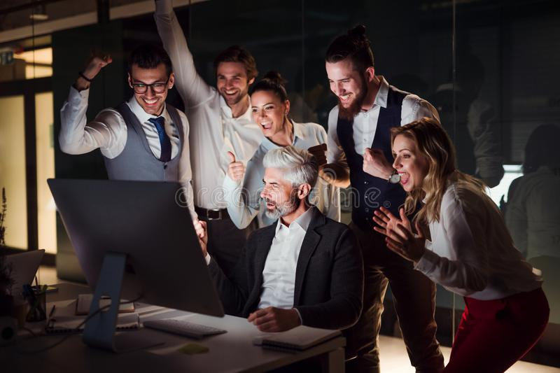 A group of business people in an office at night, expressing excitement. royalty free stock image