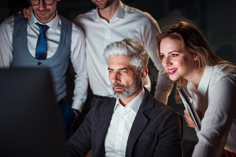 A group of business people in an office at night, using computer. royalty free stock image
