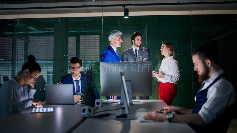 A group of business people in an office at night, using computer. royalty free stock photography