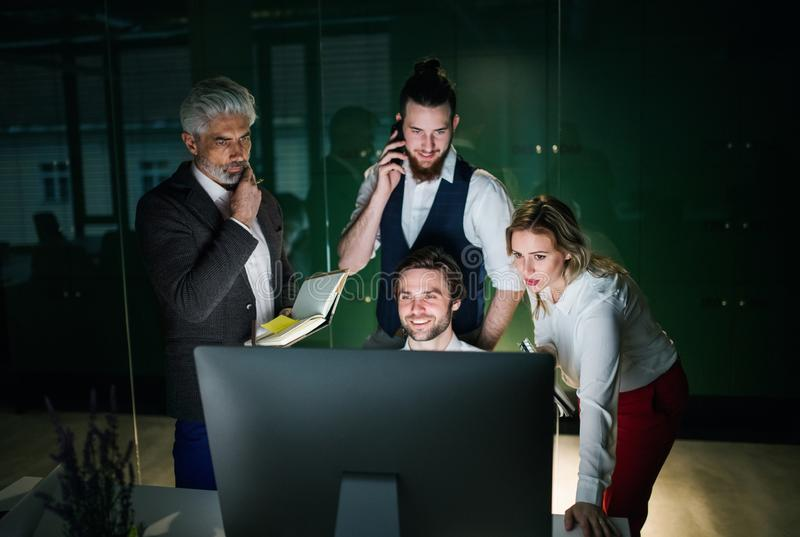 A group of business people in an office at night, using computer. stock image