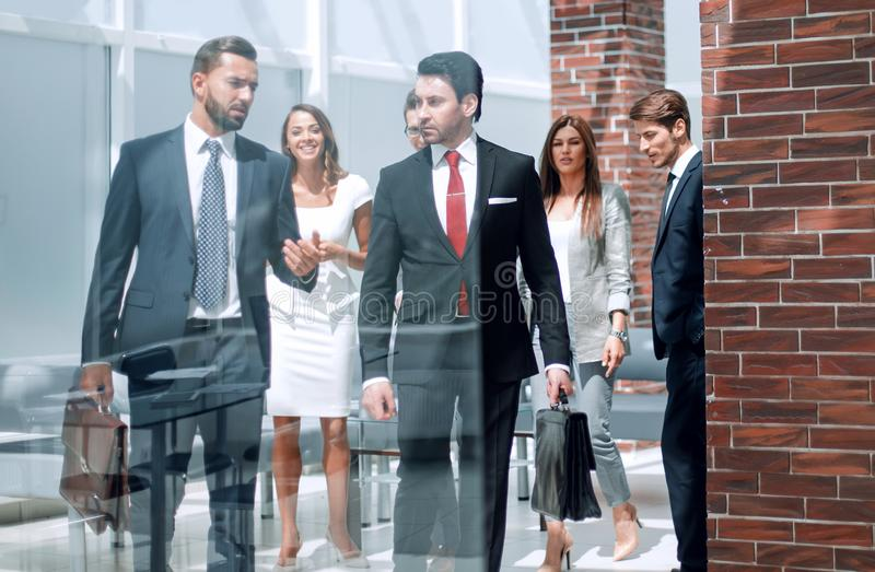 Group of business people passing through the lobby of the business center royalty free stock photo