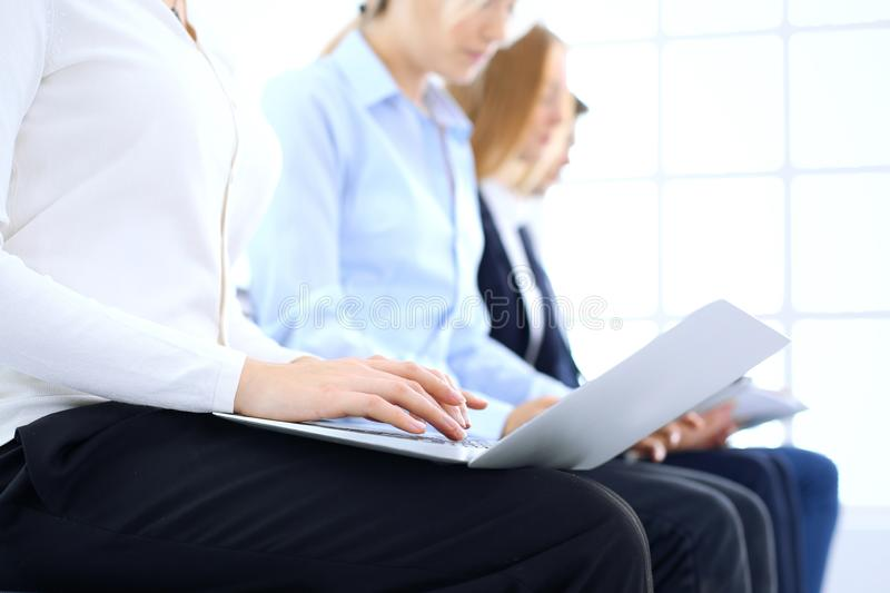 Group of business people sitting in office waiting for job interview, close-up. Hands of woman working on laptop. Group of business people sitting in office stock photos