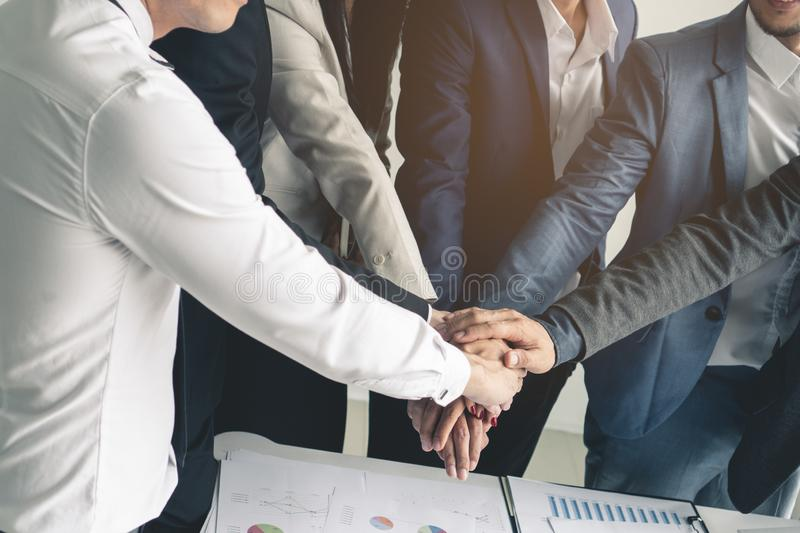 People stacking hands together showing power of teamwork stock image