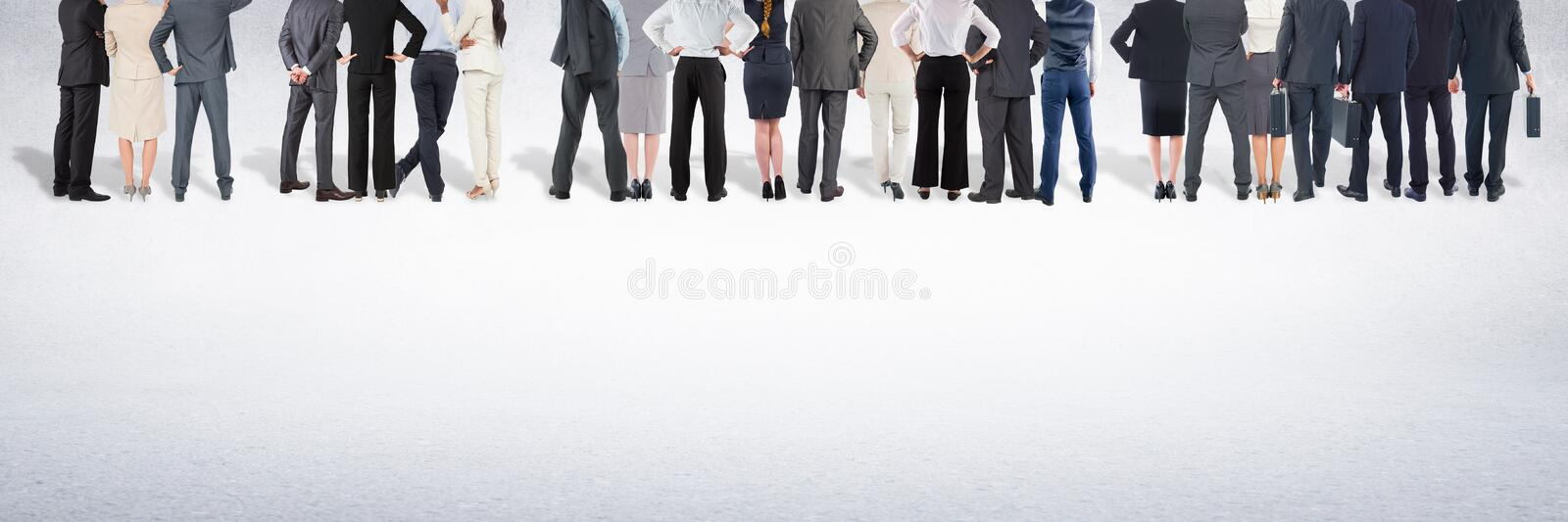Group of business people standing in front of blank grey background royalty free stock photography
