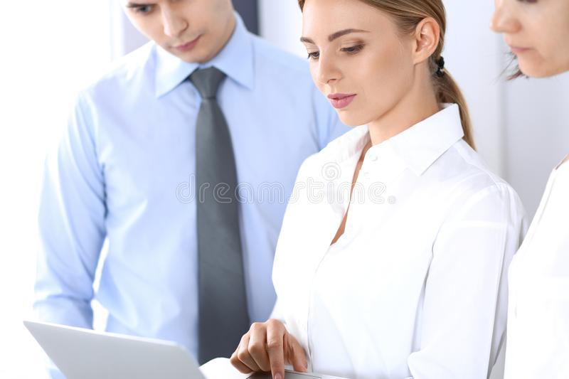 Group of business people using laptop computer while standing in office. Meeting and teamwork concept royalty free stock photography
