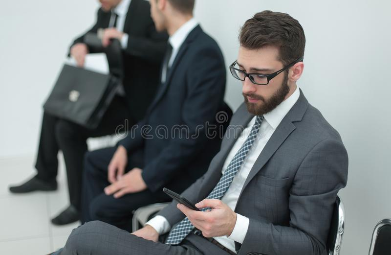 Group of business people waiting for a meeting sitting in the office reception. stock photography