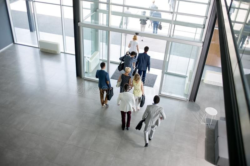Group of business people walking from building stock images